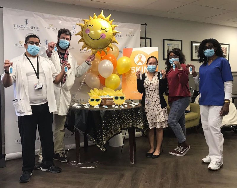 Group of employees standing around a table with a sunshine balloon